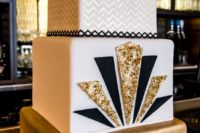 21 a chic square cake with a gold layer, a white layer decorated with black and gold glitter triangles and a gold and white chevron layer
