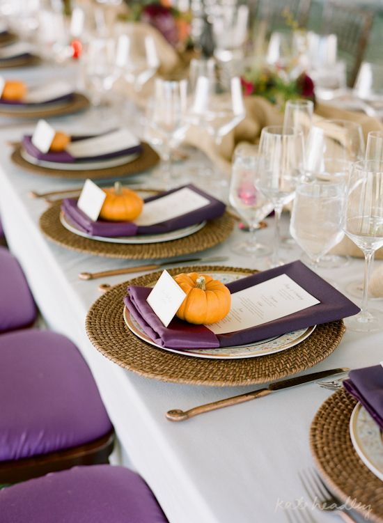 a fall table setting with purple napkins, menus and chairs, pumpkins for card holders