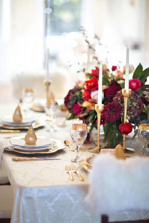 gold candle holders, gold rim glasses and red florals for a gorgeous wedding tablescape