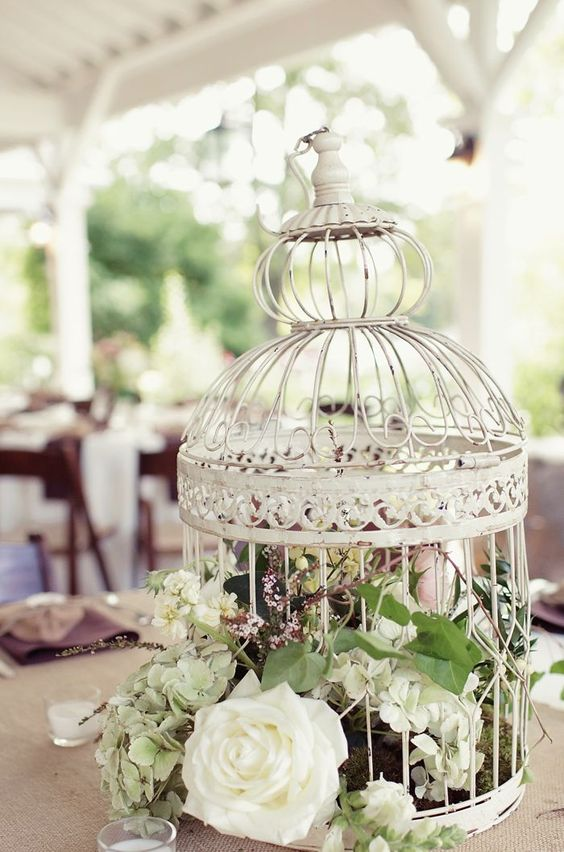 white cage with lush florals and greenery for a rustic wedding centerpiece