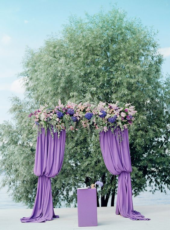 a purple wedding arch with curtains, lush blooms and greenery looks very eye-catching