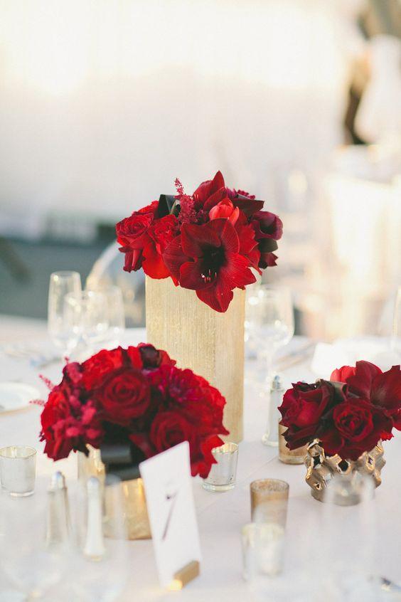 heiße rote Blüten in gold Vasen mit schwarzem Band für eine schicke Hochzeit Tischdekoration