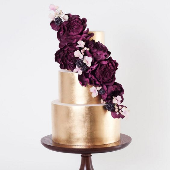 Picture Of a metallic gold wedding cake topped with plum blooms ...