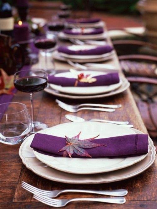 eine Rustikale wedidng tablescape mit einem lila Tischläufer, Servietten und Blätter fallen