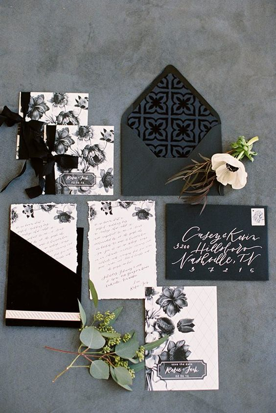 black and white wedding stationery with floral prints and black ribbon bows for a classic or organic wedding