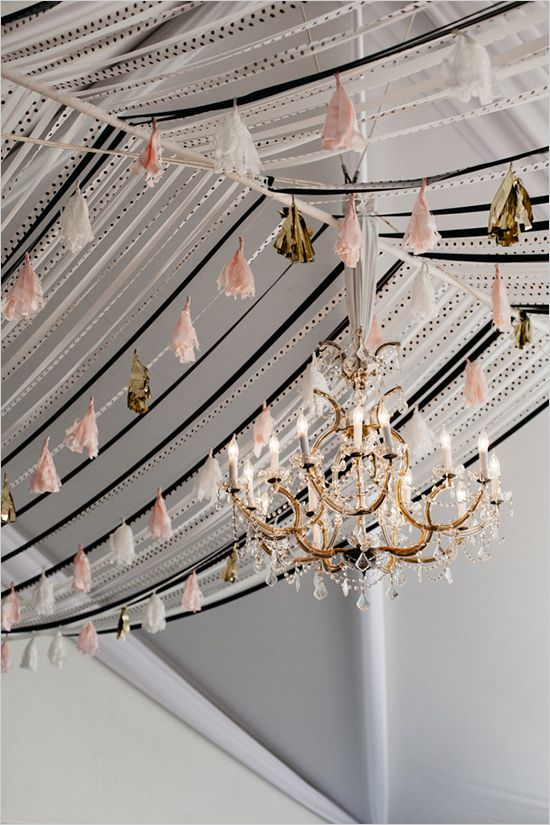 handmade tassel garlands over the reception and a large glam chandelier that fits the look
