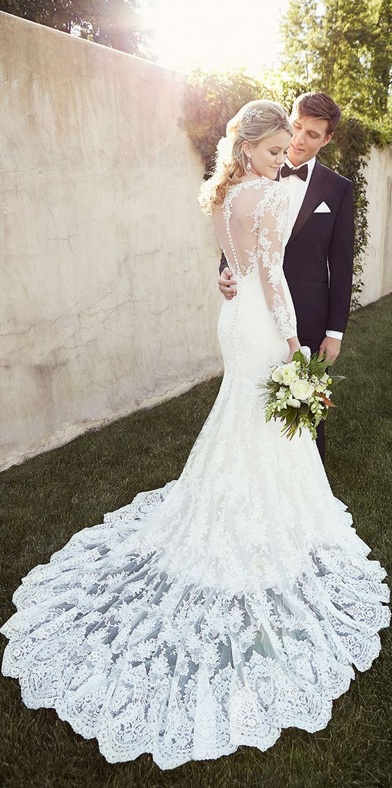 long sleeve mermaid wedding dress with a sheer and lace illusion back on a row of buttons and a lace overskirt