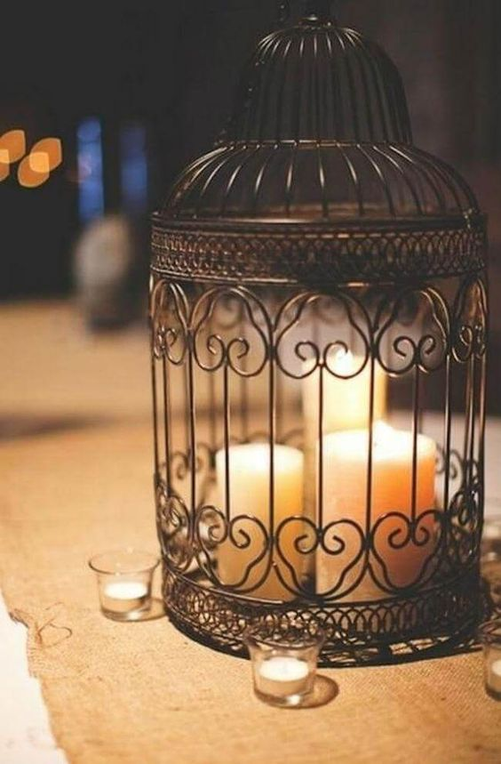 a black birdcage used as a large candle holder for several candles
