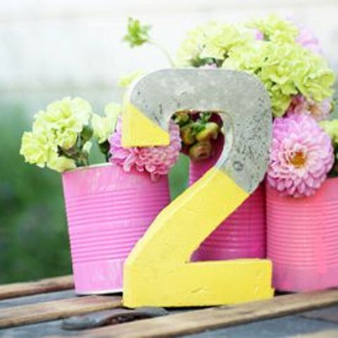a color block concrete table number and bold pink tin cans as flower vases