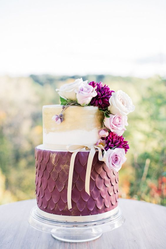 a unique cake with gold leaf decor, purple scallops and pink and purple blooms on top