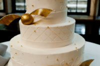25 a chic wedding cake in white with gold beads and gold snitches