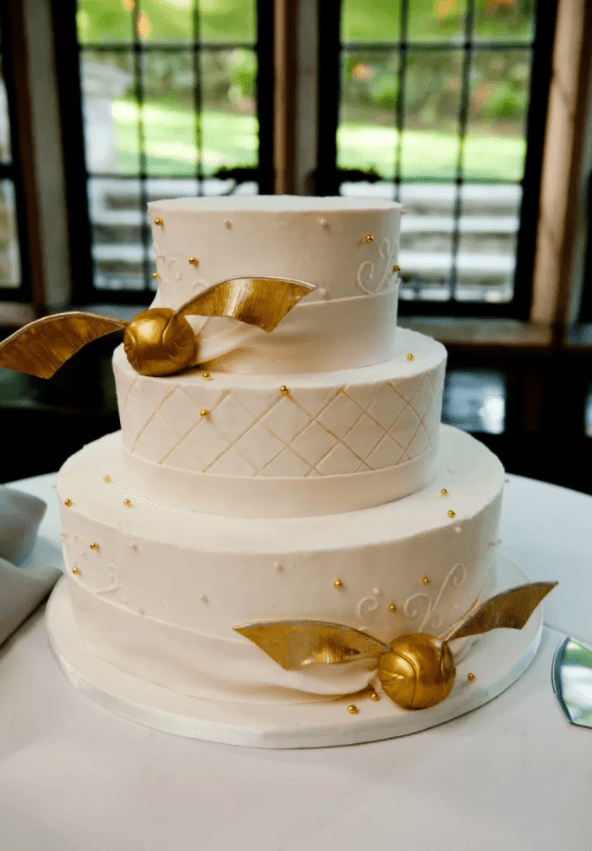 a chic wedding cake in white with gold beads and gold snitches