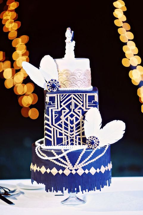 a cobalt blue and white wedding cake with rose scallops, beads, feathers and vintage brooches