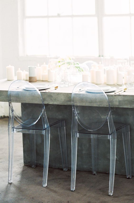 a concrete dining table with lots of candles and acrylic chairs are a great combo for a minimalist wedding