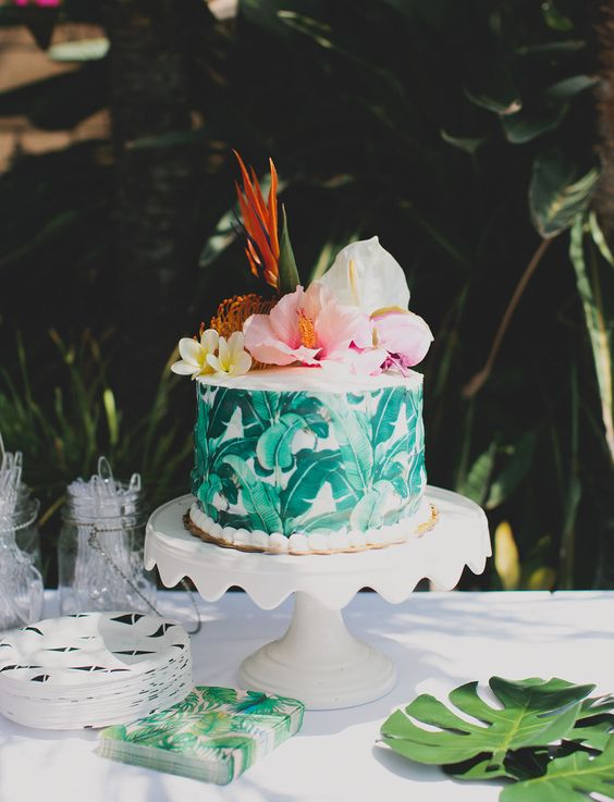 a banana leaf wrapped cake, paired with hibiscus, bird of paradise, and monstera leaves