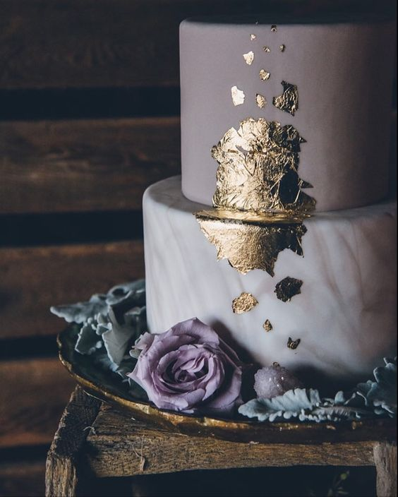 a matte lavender and a marble wedding cake topped with gold leaf and a pale lavender rose
