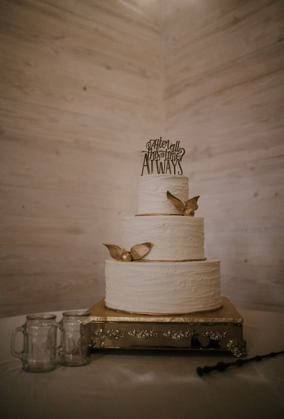 a textural white wedding cake with gold snitches and a cake topper