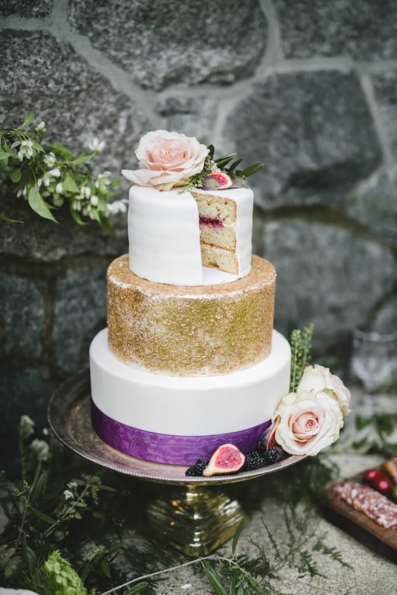 a wedding cake with a white layer, a gold glitter layer and a white layer with a purple ribbon