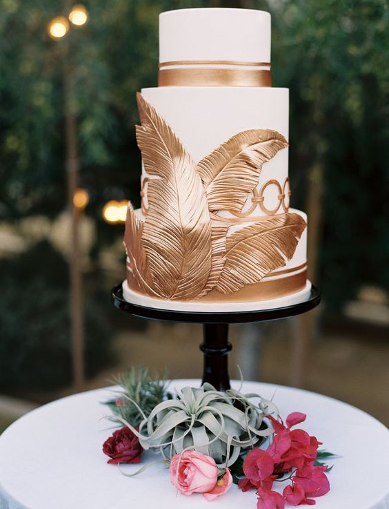 a wedding cake with gold tropical leaves and stripes for an elegant look