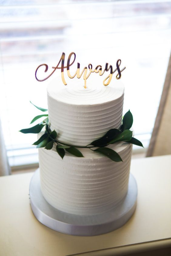 a white textural wedding cake topped with greenery and an Always topper