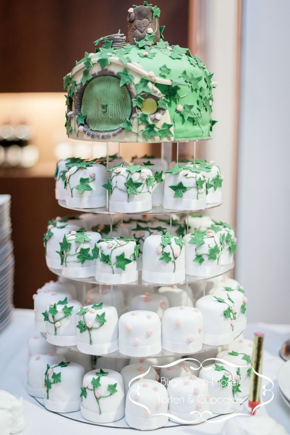 hobbit-inspired wedding cake with matching cupcakes looks unique