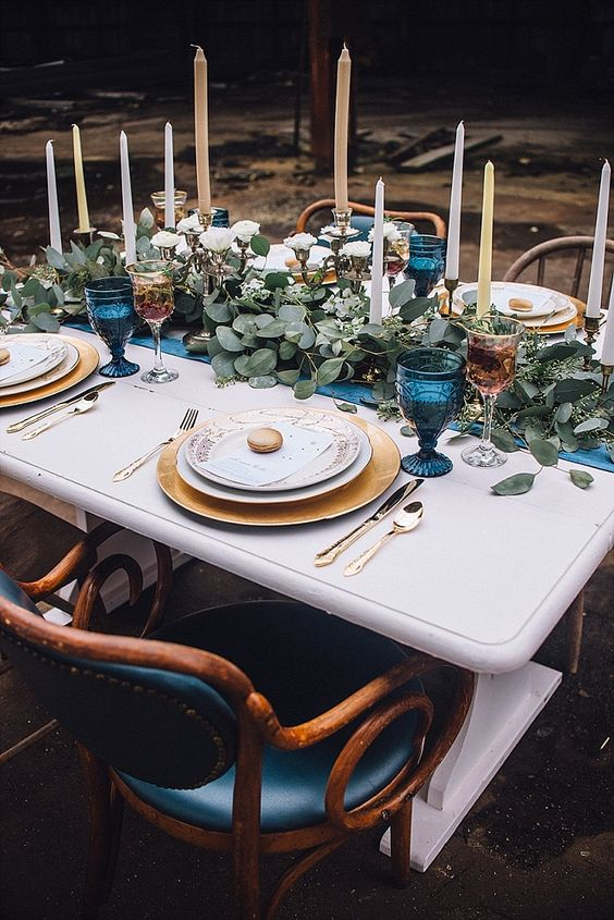 wedding table setting with an indigo table runner and glasses, a leafy table runner