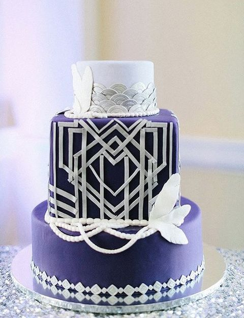 a silver and purple wedding cake with geo details, scallops and feathers