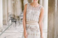 28 a sleeveless wedding dress with an illusion neckline and gold beading and embroidery