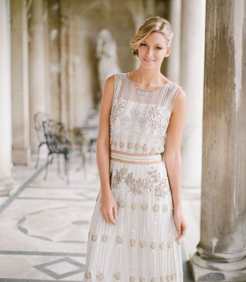 a sleeveless wedding dress with an illusion neckline and gold beading and embroidery