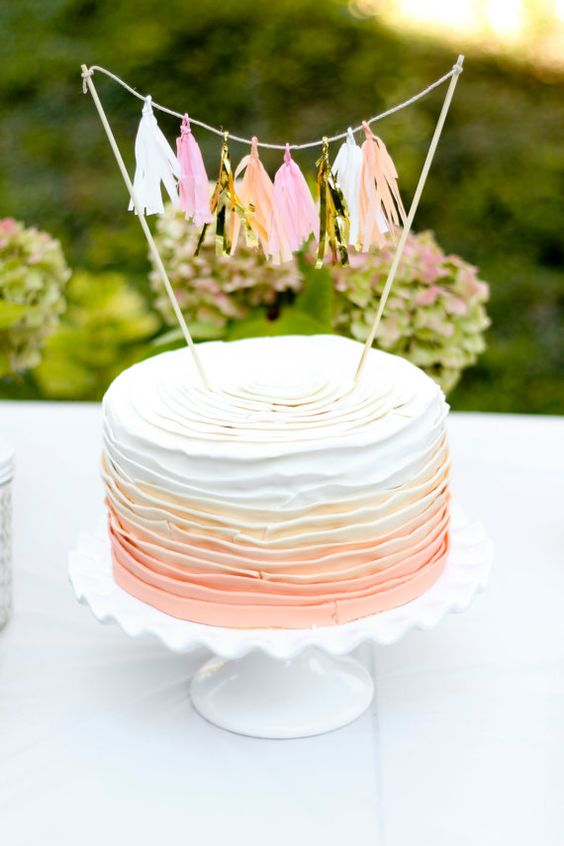 a tassel garland topper for a layered ombre cake looks cute and glam