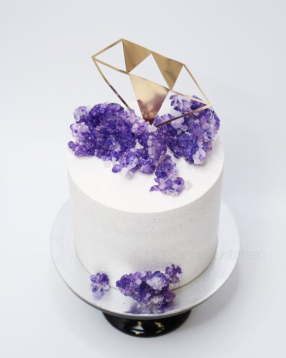 a white wedding cake with a gold diamond topper and purple sugar amethysts
