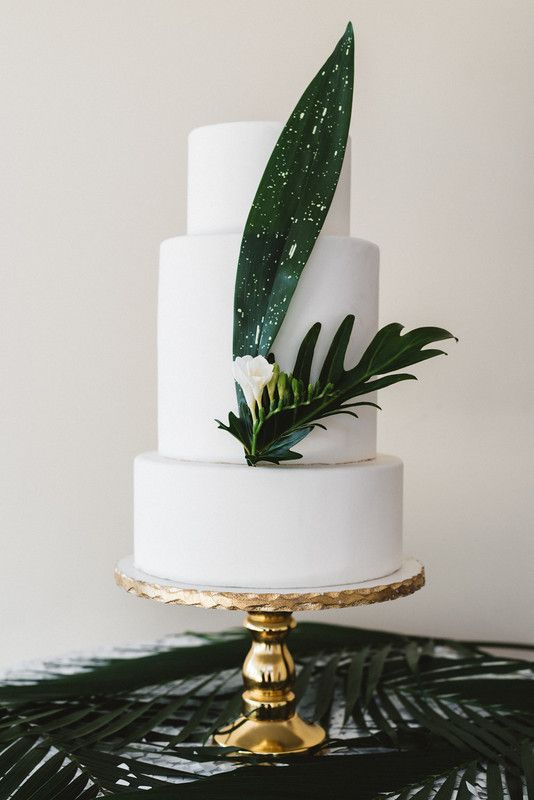 an exquisite white wedding cake decorated with tropical leaves and a single white bloom
