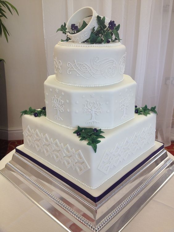 cream wedding cake with rings on top, edible greenery and leaves and textural images