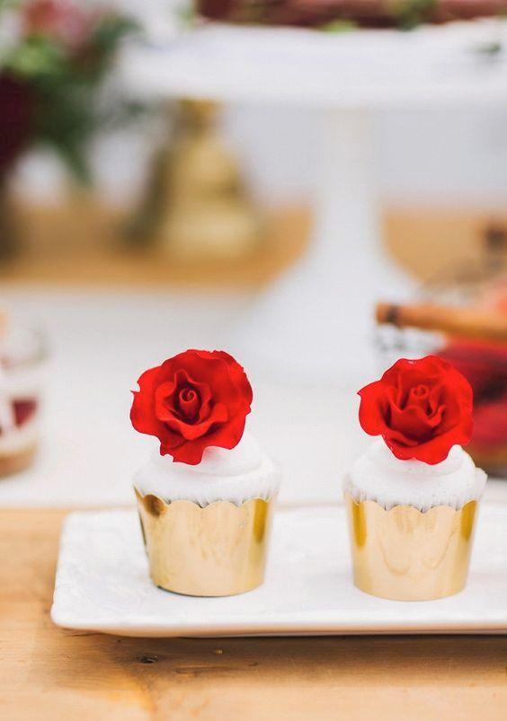 cremige cupcakes garniert mit roten Rosen und in Goldfolie