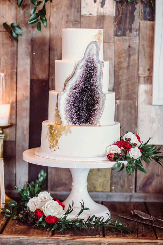 a white wedding cake with gold leaf decor and an amethyst geode part