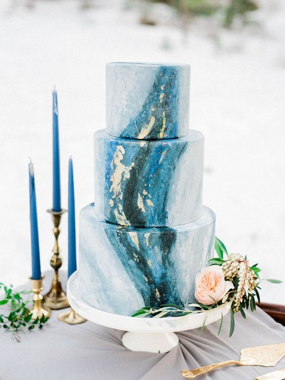 an indigo and gold leaf wedding cake and indigo candles for an accent