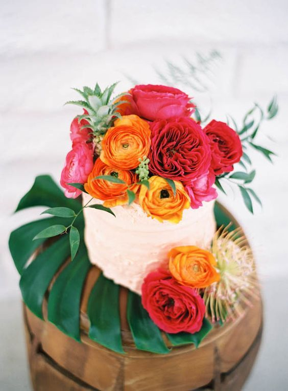 display your wedding cake on a large tropical leaf, top it with bold blooms