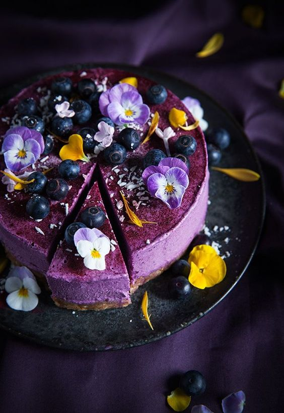 purple wedding cheesecake with edible flowers and blueberries