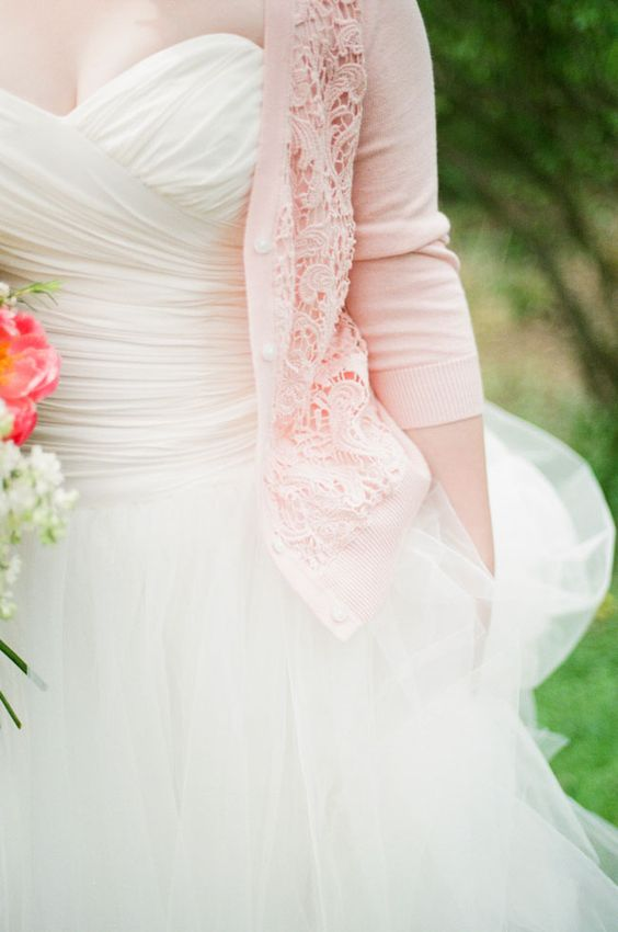 strapless wedding dress with a pink wedding cardigan with lace detailing and pearl buttons