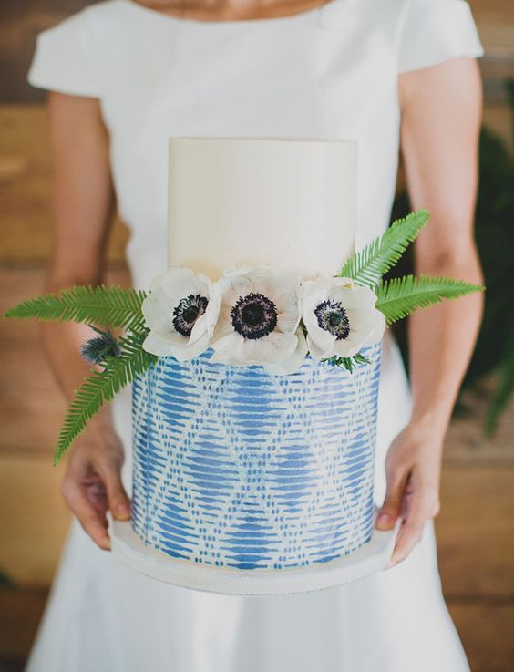 a wedding cake with a creamy layer and a patterned indigo one, topped with blooms