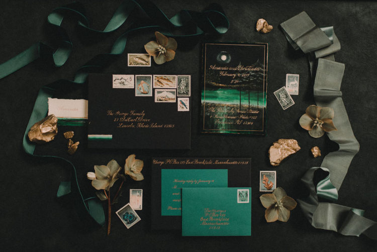The luxurious wedding invitation uite in emerald and black with gold calligraphy