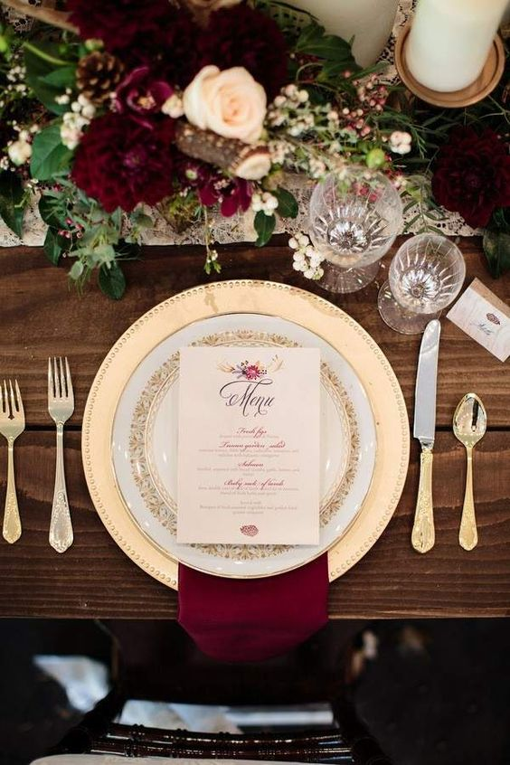 a very elegant table setting with gold chargers and cutlery, burgundy blooms and napkins