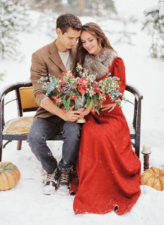 vintage-inspired red wedding dress with long sleeves anda faux fur scarf on top to feel warm