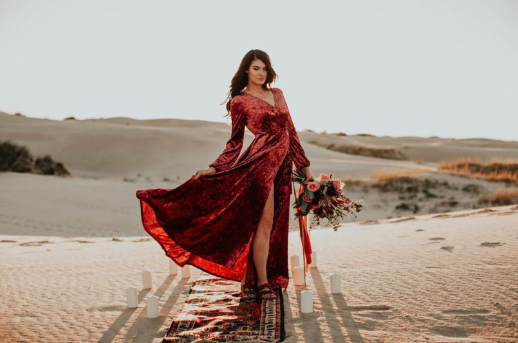 She also had a wrap red crushed velvet dress on, and it looked just jaw-dropping in the backdrop of white dunes