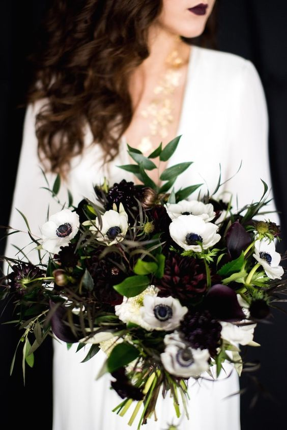 a moody bouquet with deep purple and white blooms and greenery