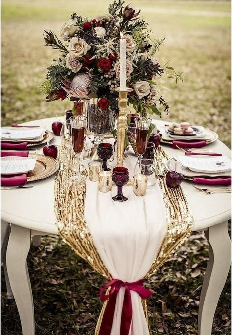 glam wedding tablescape with burgundy glasses, napkins and a gold sequin table runner