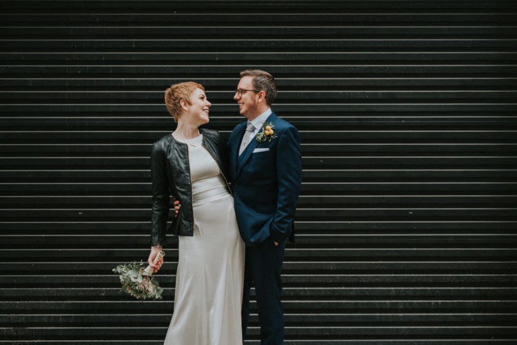 She covered up with a black leather jacket, and the groom was wearing a navy blue three-piece suit
