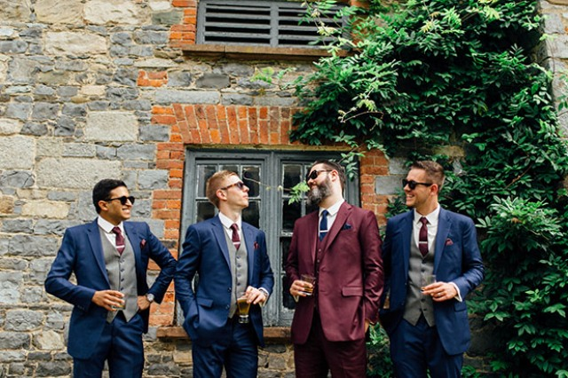 The groom was wearing a chic burgundy suit with a navy tie, and the groomsmen were rocking navy suits with burgundy ties and grey vests