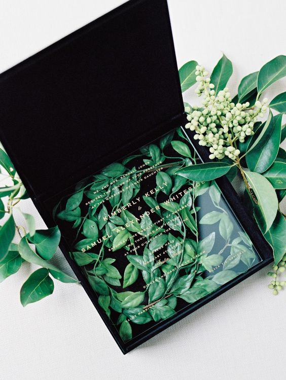 a black velvet box filled with greenery and with an acrylic invite on top looks very refined yet modern