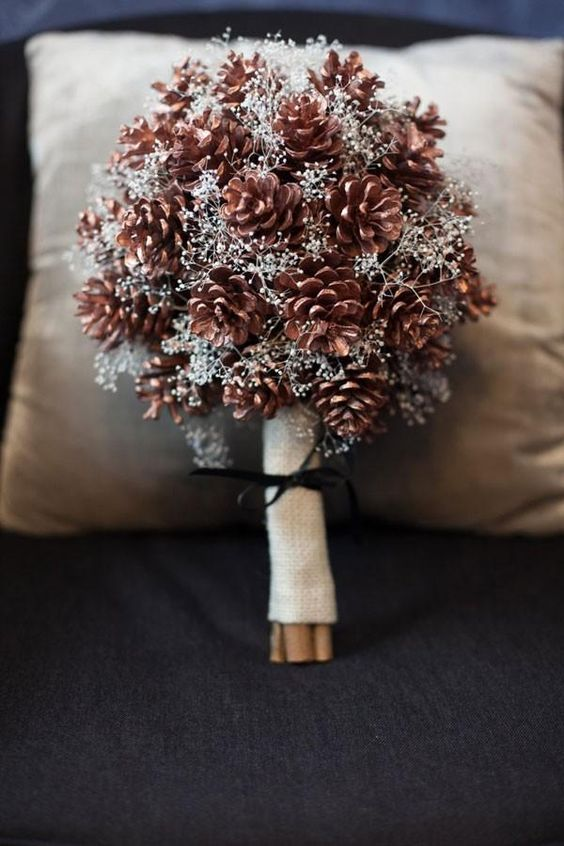 a pinecone and silver foliage wedding bouquet with a burlap wrap and a black ribbon bow